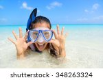 Small photo of Beach vacation fun woman wearing a snorkel scuba mask making a goofy face while swimming in ocean water. Closeup portrait of Asian girl on her travel holidays. Summer or winter destination.