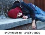 Small photo of young homeless boy sleeping on the street