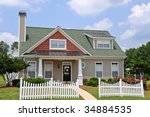 Cottage Style Home with White Fence and Gazebo - stock photo