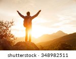 Stock photo hiker with backpack stands on che rock cliff in the mountains over the rising sun 348982511