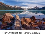 Snow-capped mountains, calm glacial lake, rocks and log on the foreground