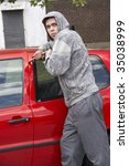 Young Man Breaking Into Car - stock photo