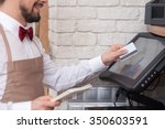 Small photo of Close up of skillful male cafe worker is swiping credit card through the screen. He is holding a checkbook and smiling