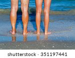 Small photo of Healthy male and female legs feet on the sandy shore on the blue sea background