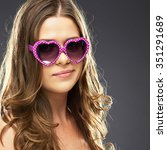 Small photo of Close up face portrait of woman with sarcasm and contempt for the heart-shaped glasses.