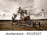 Oil pums in the fields vintage rusty colour against moody cloudscape - stock photo