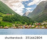 A lots of little colorful traditional Norwegian houses near the sea with green forest on mountains on background and blue sky with dark clouds, Sognefjord, Norwa - stock photo