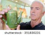 man looking at antique tea pot | Shutterstock . vector #351830231
