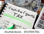 Small photo of Notebook with capital gains tax sign on a table. Business concept.