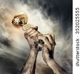 gold cup in dirty hands on sky... | Shutterstock . vector #352025555