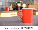 red mug on the table in kitchen. | Shutterstock . vector #35220490