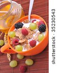 bowl of muesli with fruits and honey, healthy breakfast - stock photo