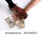 Brown shoes over a hand trying to reach money.  Concept of power, force, big brother. - stock photo