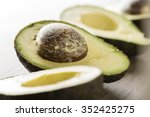 avocados on a wooden table.... | Shutterstock . vector #352425275