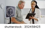 black woman doctor talking with ... | Shutterstock . vector #352458425