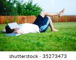 Small photo of Young man is laying on green ground and learning