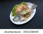 Small photo of Steamed snapper with lemon on black background.