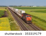 Container train on one of two tracks crossing colorful prairie - stock photo