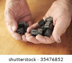 printer's ink-stained hands holding metal type pieces - stock photo