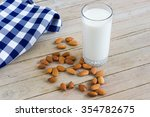 a glass of milk with almonds... | Shutterstock . vector #354782675