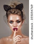 Small photo of portrait of beautiful young blonde girls, with glowing skin, beautiful makeup and very puffy kissable lips,with cat ears on her head and veil, the netting on face with professional retouching