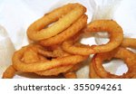 Small photo of Golden brown deep fried Onion Rings set on paper towel to absorb grease