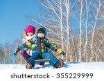 Two Cute Kids Riding Sled And...