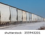 Long line of rail cars in winter snow - stock photo
