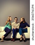 Stock photo a shy young man sitting on the couch with two attractive girls beauty fashion 356076194
