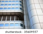 Curved golden skyscraper detail reflecting a blue sky. - stock photo