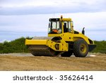 Yellow road roller at work - stock photo