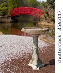 An old stone birdbath with a colorful bridge in the background. - stock photo