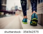 Stock photo woman athlete feet and shoes while running in the city 356562575
