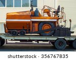 Small photo of A paver finisher, asphalt finisher or paving machine waiting to be transported on a road being asphalted