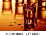 drink shots with reflection and drops in warm light - stock photo