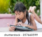 Young Girl Using Tablet Outdoo...