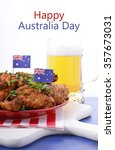 Small photo of Happy Australia Day barbeque setting with spicy chicken wings with red, white and blue color theme with glass of beer.