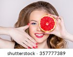 Small photo of the girl's portrait with a smile upon the face, a magnificent hairdress, red lips and nails with grapefruit. Advertizing of cosmetics and healthy lifestyle