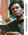 Small photo of Young black man with little black address book in a London street