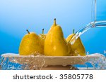 Water pouring on yellow pears. - stock photo