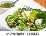 Close up of organic green salad with walnut and lime-pepper dressing - stock photo