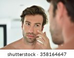 handsome man applying facial... | Shutterstock . vector #358164647