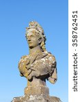 Small photo of Old weathered stone bust of Marianne, a symbol of France and the French Republic, allegorical of Freedom and Reason, covered in colorful lichen against a blue sky