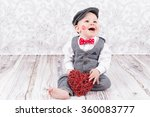 Small photo of lovely baby boy in barret with lipstick kiss on his cheek and red heart