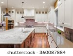 Stock photo beautiful kitchen in new luxury home with wrap around cabinets hardwood floors pendant lights 360087884