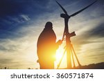 Small photo of Silhouette of a male surveyor standing with theodolite against electric generator and evening sky while measuring the distance for the construction of a new highway, man geo desist working outside