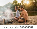Three friends having fun at the beach. They are sitting around a campfire with a lot of smoke, doing a barbecue with skewers  A shirtless man with beard and hat is playing a ukulele. - stock photo