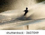 Silhouette of a barefoot skier with backlit water spray - stock photo