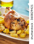 Small photo of Pork shank with roasted potatoes on a white serving plate.
