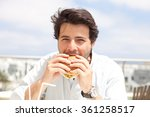 young man eating a hamburger | Shutterstock . vector #361258517